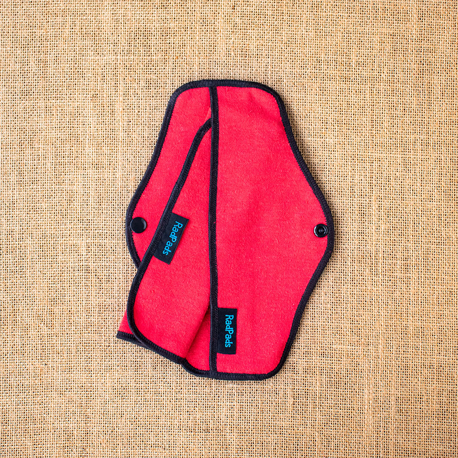 A red hemp fleece outer case of a reusable cloth menstrual pad with a towel insert halfway in place